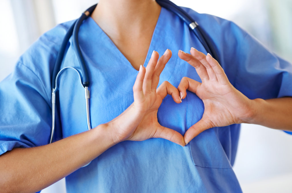 Cropped image of a nurse making a heart shape with her hands